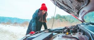 woman in winter checking car under the hood
