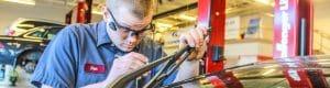 mechanics checking wiper blades on car